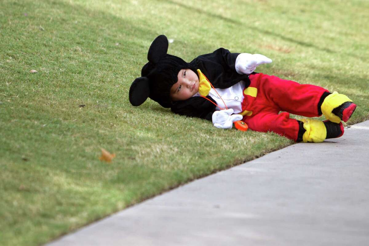 James De La Rosa lies down on the grass dressed as Mickey Mouse during a special Toddler Tuesday Halloween Ball at Discovery Green Tuesday, Oct. 28, 2014, in Houston.