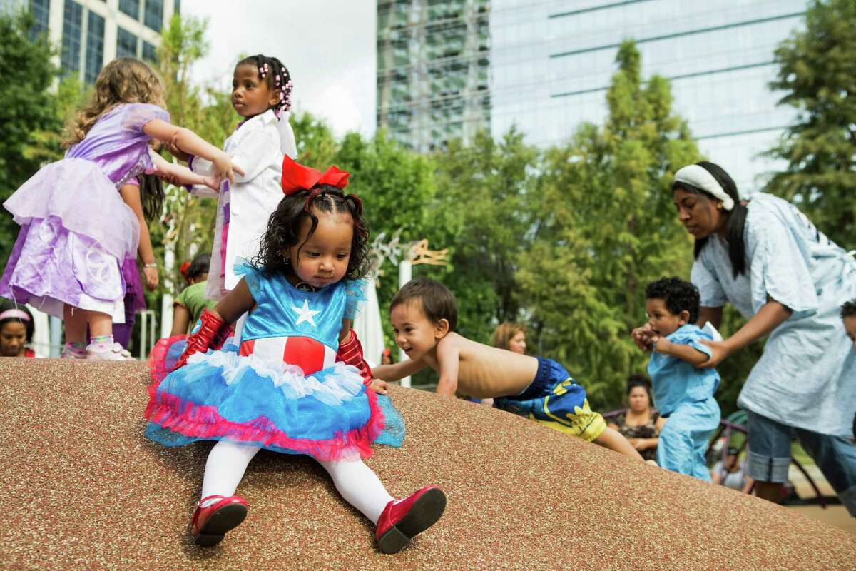 Kataleya Estrada plays on a slide as she an other children dressed in various costumes play during a special Toddler Tuesday Halloween Ball at Discovery Green Tuesday, Oct. 28, 2014, in Houston. Children were treated to story time, dancing and a costume contest during the midday event.