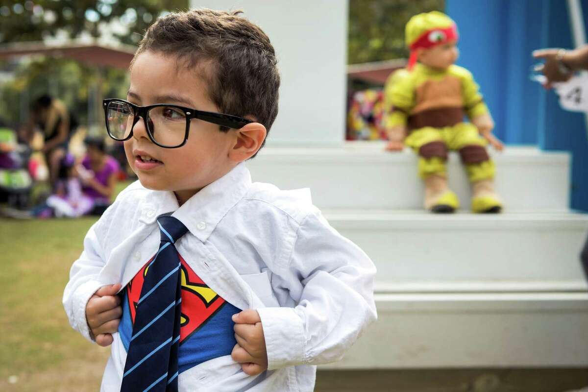 Sebastian O'Con, dressed as Clark Kent, pulls open his shirt to reveal his Superman costume underneath during a special Toddler Tuesday Halloween Ball at Discovery Green Tuesday, Oct. 28, 2014, in Houston. Children were treated to story time, dancing and a costume contest during the midday event.