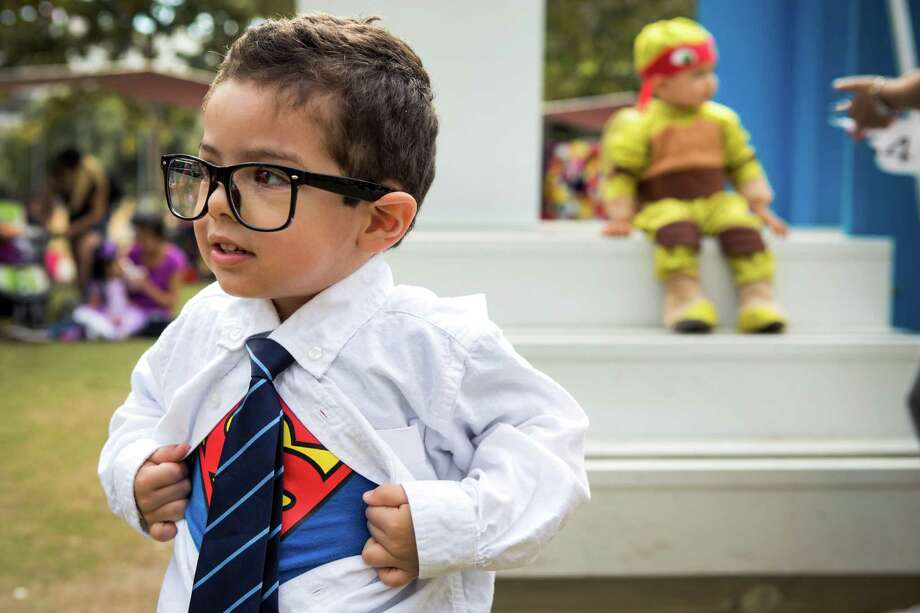 Sebastian O'Con, dressed as Clark Kent, pulls open his shirt to reveal his Superman costume underneath during a special Toddler Tuesday Halloween Ball at Discovery Green Tuesday, Oct. 28, 2014, in Houston. Children were treated to story time, dancing and a costume contest during the midday event. Photo: Brett Coomer, Houston Chronicle / © 2014 Houston Chronicle