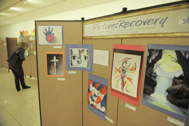 Visitors look over the work at the Recovery Art Show opening at the South Concourse of the Empire State Plaza on Monday, Oct. 27, 2014, in Albany, N.Y.  The Recovery Art Show consists of over 100 pieces of artwork by individuals in recovery from mental illness involved in Office of Mental Health programs throughout New York State.   (Paul Buckowski / Times Union) Photo: Paul Buckowski, Albany Times Union / 00029198A