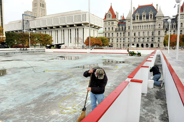 OGS worker Brian Dingman, left, sweeps debris as Joseph Johnson secures the boards for the ice skating rink on Tuesday, Oct. 28, 2014, at the Empire State Plaza in Albany, N.Y. (Cindy Schultz / Times Union) Photo: Cindy Schultz, Albany Times Union