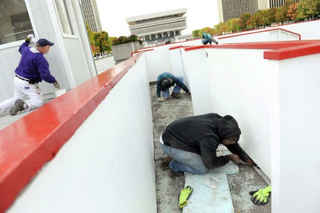 OGS worker Rick Cramer, left, paints a service building as Joseph Johnson, right, and Dave Cootware secure the boards for the ice skating rink on Tuesday, Oct. 28, 2014, at the Empire State Plaza in Albany, N.Y. (Cindy Schultz / Times Union) Photo: Cindy Schultz, Albany Times Union