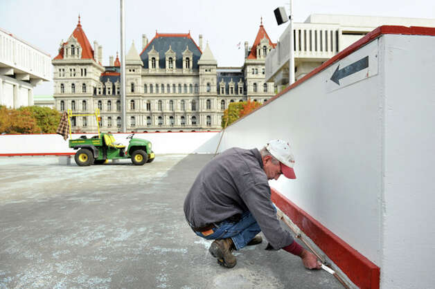 OGS worker Rob Fix tools off caulk at the base of the boards for the ice skating rink on Tuesday, Oct. 28, 2014, at the Empire State Plaza in Albany, N.Y. (Cindy Schultz / Times Union) Photo: Cindy Schultz, Albany Times Union