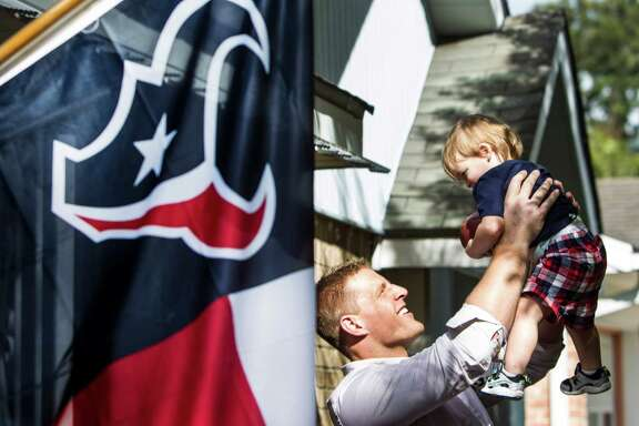 Houston Texans defensive end J.J. Watt lifts Grady Quesada into the air after Watt delivered pizza to contest winner Cody Beavers for a pizza party on Tuesday, Oct. 28, 2014, in Houston.