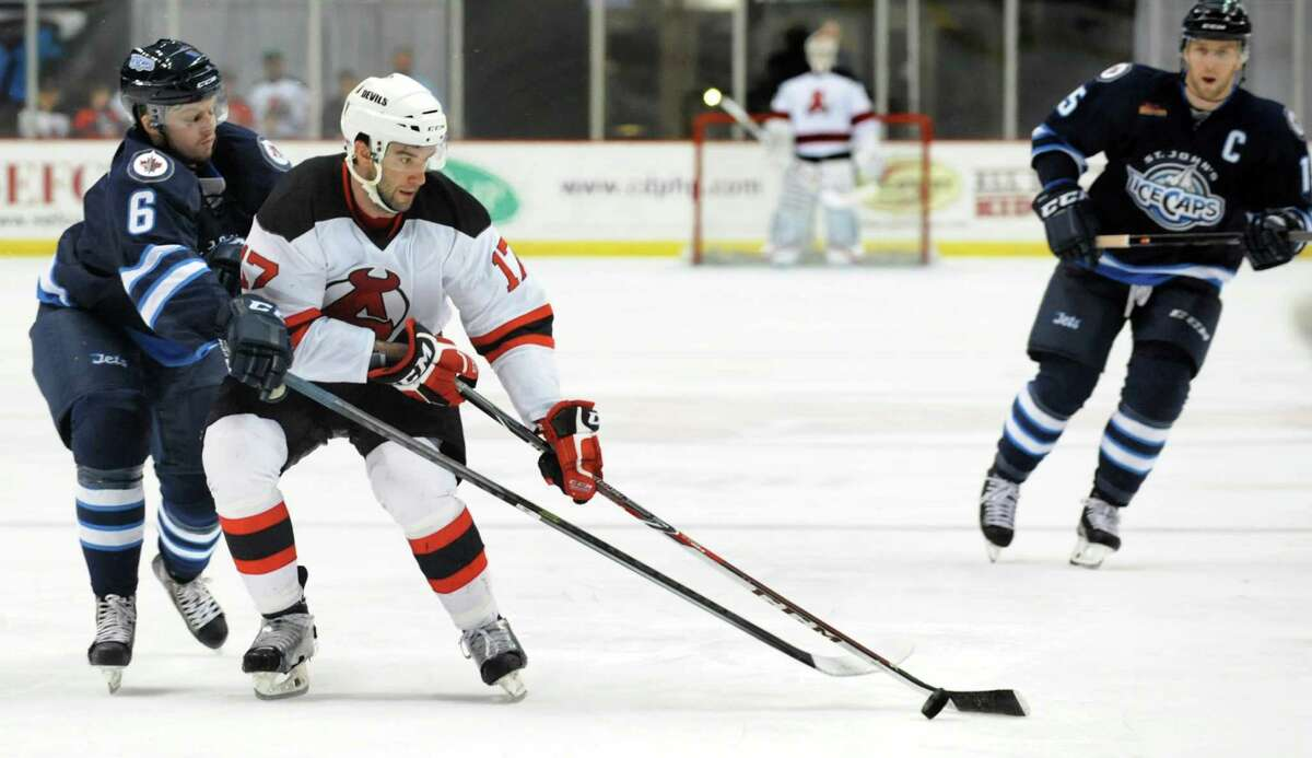 Devils' Scott Timmins, center, and IceCaps' Josh Morrissey, left, battle for the puck during their first-round playoff hockey game on Friday, April 25, 2014, at Times Union Center in Albany, N.Y. (Cindy Schultz / Times Union)