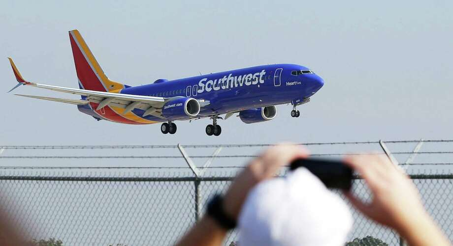 A Southwest Airlines plane with a new paint job flies over Love Field in Dallas. Southwest will begin nonstop service from San Antonio to Mexico City on Sunday, taking over the route previously operated by AirTran Airways. Photo: LM Otero / LM Otero / Associated Press / AP