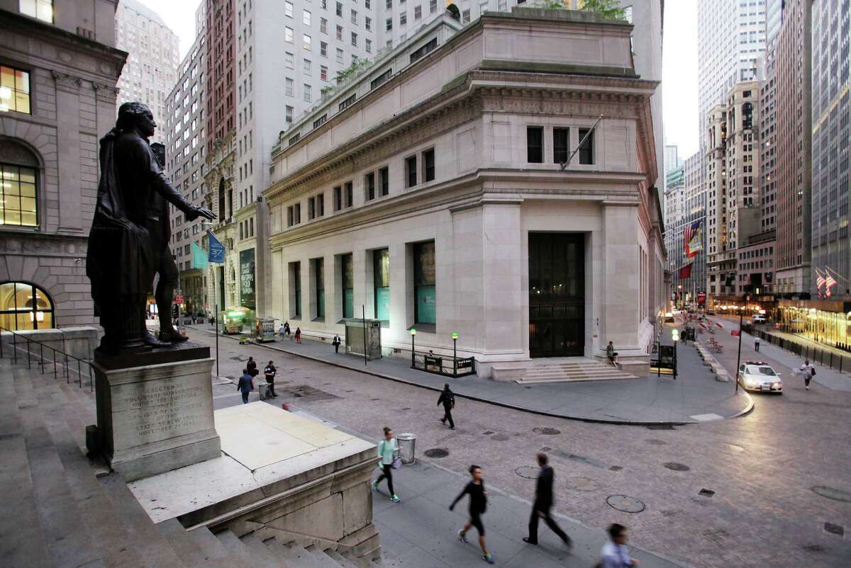 In this Oct. 8, 2014 photo, people walk to work on Wall Street beneath a statue of George Washington, in New York. U.S. stocks rose early Tuesday, Oct. 28, 2014, as investors weighed earnings reports from several companies and awaited news from a two-day U.S. Federal Reserve meeting that ends tomorrow. (AP Photo/Mark Lennihan) ORG XMIT: NYBZ144