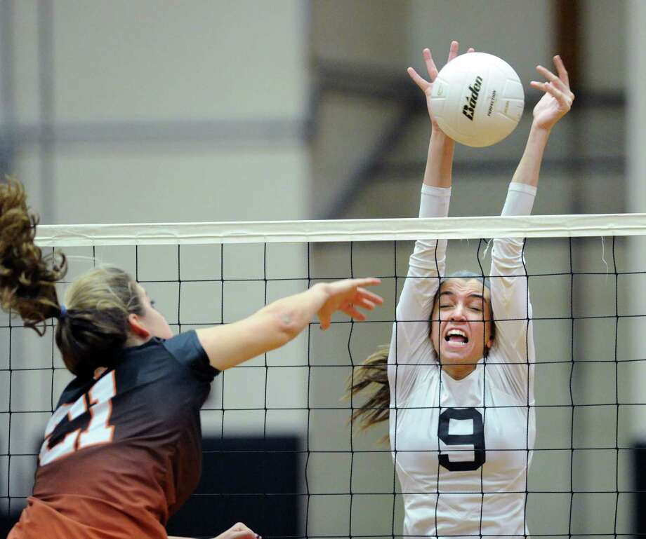 At left, Stamford's Anne Eilersten (#21) gets her spike blocked by Trumbull's Alyssa Breunig (#9) during the FCIAC semifinal girls high school volleyball match between Stamford High School and Trumbull High School at Stamford, Conn., Tuesday, Oct. 28, 2014. Trumbull won the match, 3-2, taking game 5, 15-9, for the victory. Photo: Bob Luckey / Greenwich Time