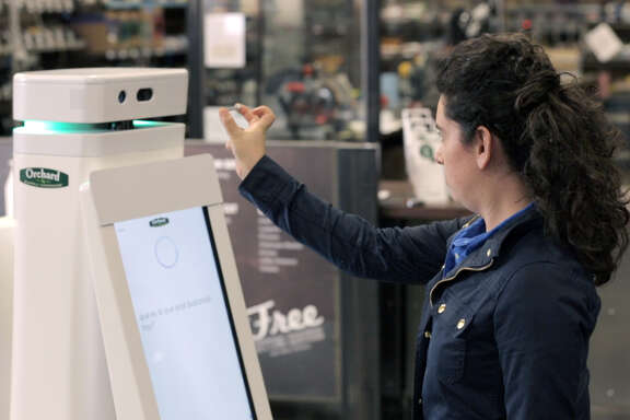 In this demonstration photo provided by Lowe's, a woman holds a nail up to be scanned by an OSHbot robot, which can identify items and lead customers to the aisle where what they're looking for is located.