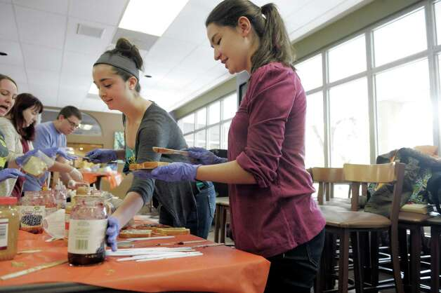 College of Saint Rose freshmen, Jackie Brochu, left, from Douglas, MA and Emily Barcia-Varno from Bethlehem make sandwiches at the PB & Jams event at the college on Tuesday, Oct. 28, 2014, in Albany, N.Y.  The Saint Rose Student Association sponsored the peanut butter and jelly sandwich event, where students, faculty and staff volunteered their time to make over 3,500 sandwiches.  The sandwiches will go to three area shelters for them to distribute.  This is the fourth year of the event.  The first year of the event 1,000 sandwiches were made.  Organizers said that the goal every year is to increase the numbers.  Cap Com FCU, Freihofer's, and Price Chopper along with other businesses donated the food supplies for the event.  (Paul Buckowski / Times Union) Photo: Paul Buckowski / 00029219A