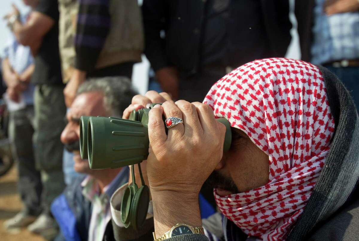 A man who says he's a refugee from Kobani watches his home town during airstrikes by the US led coalition seen from the outskirts of Suruc, near the Turkey-Syria border, Tuesday, Oct. 28, 2014. Kobani, also known as Ayn Arab, and its surrounding areas, has been under assault by extremists of the Islamic State group since mid-September and is being defended by Kurdish fighters. (AP Photo/Vadim Ghirda) ORG XMIT: XVG110