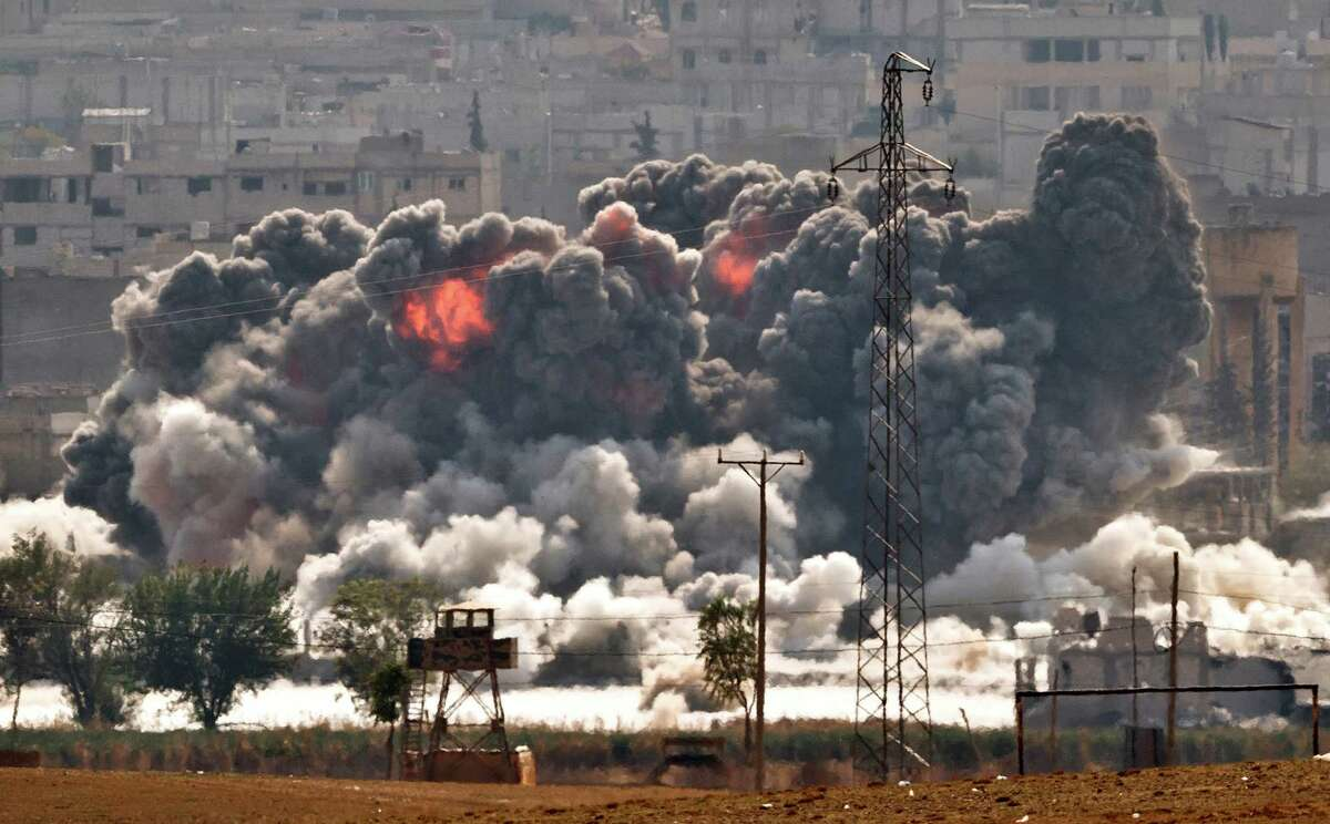 Smoke and flames rise from an Islamic State fighters' position in the town of Kobani during airstrikes by the US led coalition seen from the outskirts of Suruc, near the Turkey-Syria border, Tuesday, Oct. 28, 2014. Kobani, also known as Ayn Arab, and its surrounding areas, has been under assault by extremists of the Islamic State group since mid-September and is being defended by Kurdish fighters. (AP Photo/Vadim Ghirda) ORG XMIT: XVG102