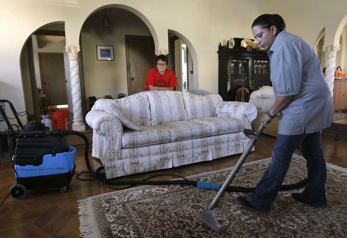 Rosa Sanchez (right), of Homejoy, steam cleans a rug for Rie Yamazaki-Bach (center) in San Francisco, Calif. on Tuesday, Oct. 28, 2014. Many homeowners are turning to Homejoy to connect with maintenance services such as carpet cleaning, plumbing and painting.