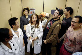 Alyssa Spencer attracts the attention of zpEd Reimann, dressed as a zombie, during an elevator ride at Samuel Merritt University on Friday, October 24, 2014. Spencer, Reimann and the other students are in their second year in the physician assistant program at the school.