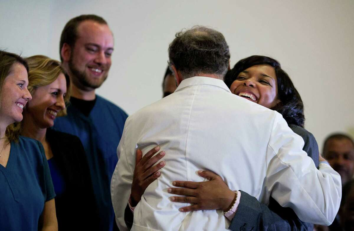 Amber Vinson, 29, the Dallas nurse who was being treated for Ebola, right, embraces Emory University Hospital epidemiologist Dr. Bruce Ribner, as she leaves a press conference after being discharged from the hospital, Tuesday, Oct. 28, 2014, in Atlanta. Vinson worked as a nurse at Texas Health Presbyterian Hospital Dallas and cared for Thomas Eric Duncan, a Liberian man who died of Ebola at the hospital on Oct. 8. Vinson was one of two nurses who became infected while caring for Duncan. (AP Photo/David Goldman) ORG XMIT: GADG101
