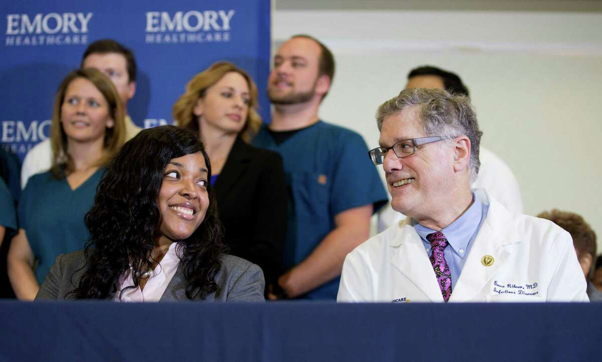 Amber Vinson, left, 29, the Dallas nurse who was being treated for Ebola, looks at Emory University Hospital epidemiologist Dr. Bruce Ribner, during a press conference after being discharged from the hospital, Tuesday, Oct. 28, 2014, in Atlanta. Vinson, is now virus-free, worked as a nurse at Texas Health Presbyterian Hospital Dallas and cared for Thomas Eric Duncan, a Liberian man who died of Ebola at the hospital on Oct. 8. Vinson was one of two nurses who became infected while caring for Duncan. (AP Photo/David Goldman) ORG XMIT: GADG102