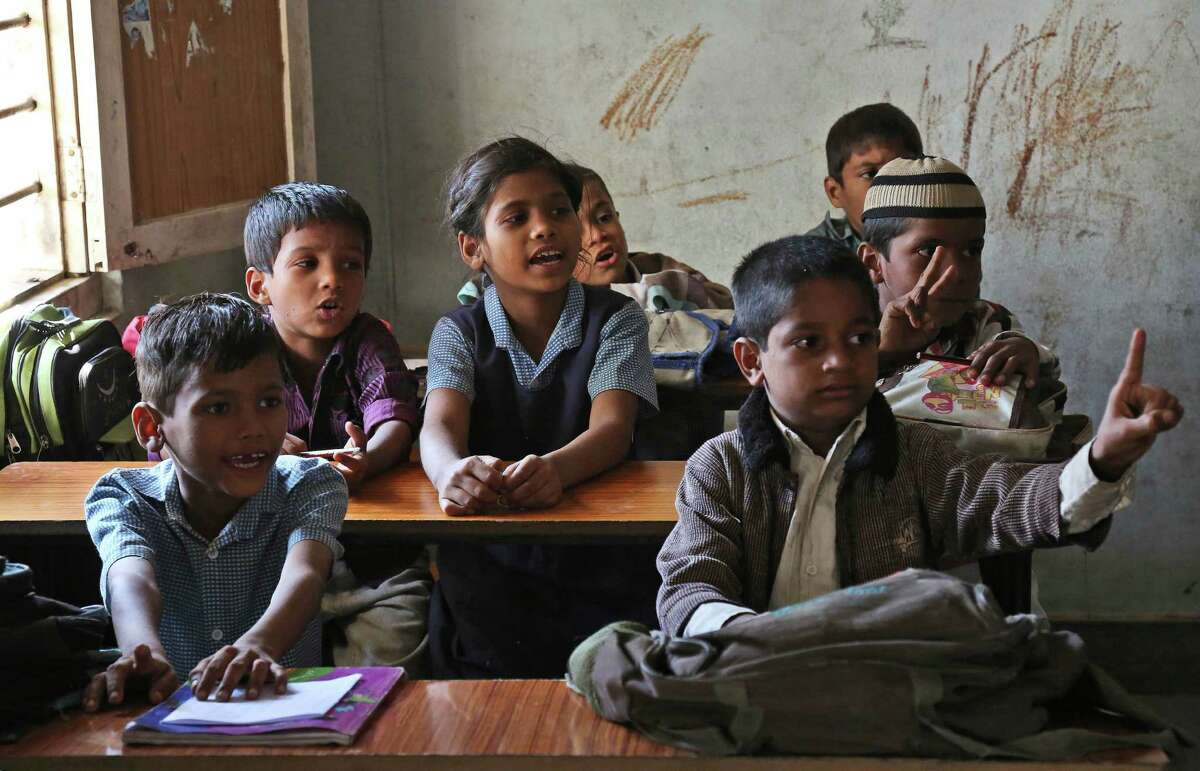 A schoolgirl sits among boys at a government school in Hyderabad, India, Tuesday, Oct. 28, 2014. Indian women still face some of the world's worst inequality in access to health care, education and work, despite years of rapid economic growth, according to the annual Gender Gap Index by the Geneva-based World Economic Forum released Tuesday. India ranked an impressive 15th for female political participation, but it was among the bottom 20 in terms of income, literacy, work force participation and infant survival. (Mahesh Kumar A.) ORG XMIT: DEL132