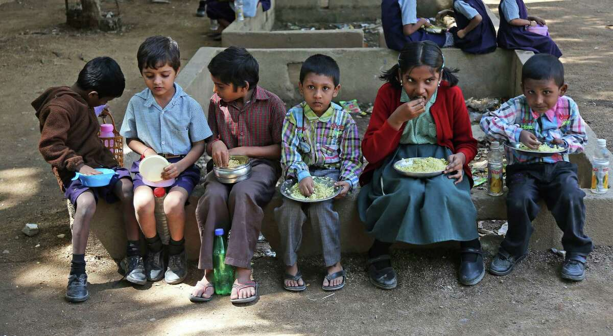 Indian school children sit outdoors and eat lunch at a government school in Hyderabad, India, Tuesday, Oct. 28, 2014. Indian women still face some of the world's worst inequality in access to health care, education and work, despite years of rapid economic growth, according to the annual Gender Gap Index by the Geneva-based World Economic Forum released Tuesday. India ranked an impressive 15th for female political participation, but it was among the bottom 20 in terms of income, literacy, work force participation and infant survival. (Mahesh Kumar A.) ORG XMIT: DEL131