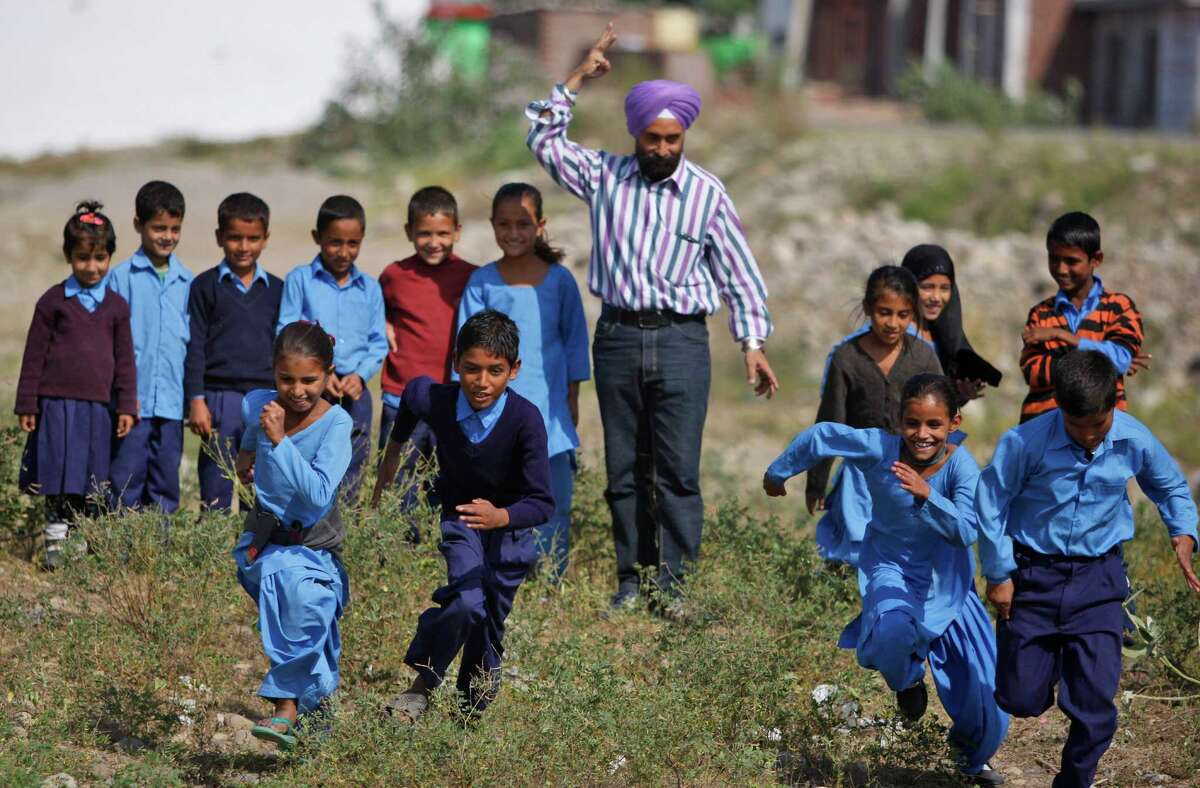 A teacher gives the count as Indian schoolchildren run a race at a government school on the outskirts of Jammu, India, Tuesday, Oct. 28, 2014. Indian women still face some of the world's worst inequality in access to health care, education and work, despite years of rapid economic growth, according to the annual Gender Gap Index by the Geneva-based World Economic Forum released Tuesday. India ranked an impressive 15th for female political participation, but it was among the bottom 20 in terms of income, literacy, work force participation and infant survival. (AP Photo/Channi Anand) ORG XMIT: DEL130