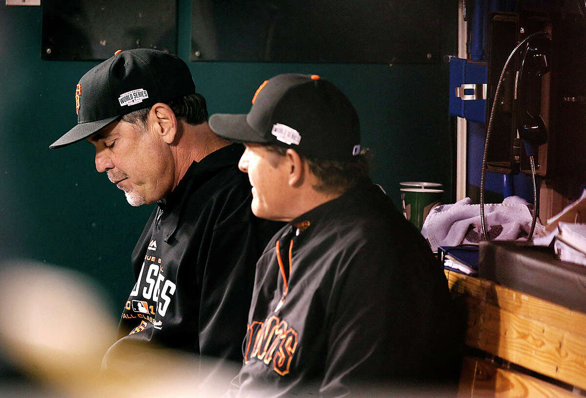 Giants manager Bruce Bochy sits with pitching coach Dave Righetti in the dugout during the third inning during Game 6 of the World Series at Kauffman Stadium on Tuesday, Oct. 28, 2014 in Kansas City, Mo.