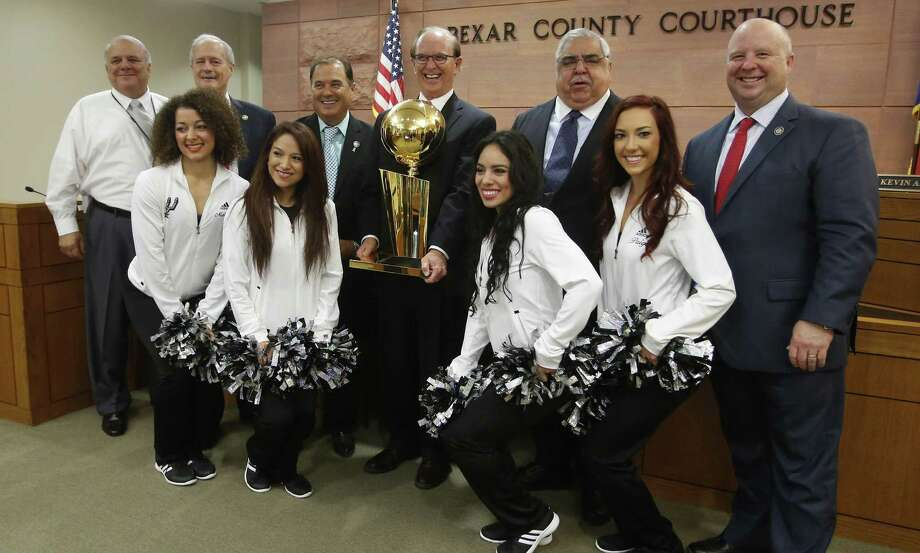 Bexar County Judge Nelson Wolff holds the Larry O'Brien Trophy and is joined by Tax Assess- or-Collector Albert Uresti (from left) and Commis- sioners Tom- my Adkisson, Sergio Rodriguez, Paul Elizondo and Kevin Wolff and several Silver Dancers. Photo: William Luther / San Antonio Express-News / © 2014 San Antonio Express-News