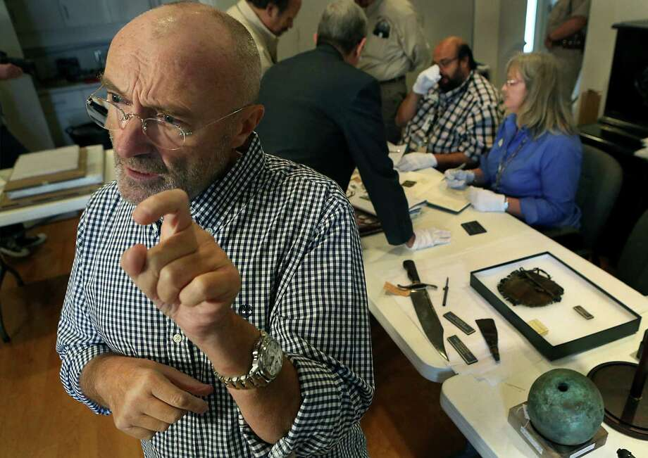 Phil Collins goes over a display of some of the more than 200 items he has collected that have ties to the Alamo. He has donated the collection to Alamo. Photo: Bob Owen / San Antonio Express-News / © 2014 San Antonio Express-News