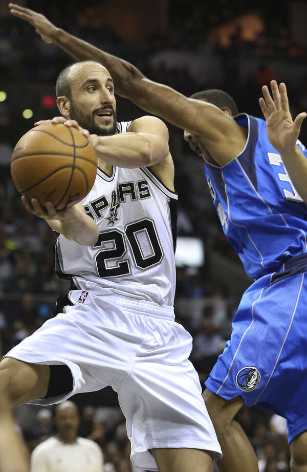 Manu Ginobili looks for an open teammate after driving under the basket in the Spurs' season-opening victory. Photo: Tom Reel / San Antonio Express-News