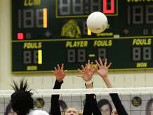 Little Cypress-Mauriceville's Malayzia Winbush, No. 13, goes for a spike against Hardin-Jefferson's Kenedy Padgett, No. 12, and Shelby Sonnier, No. 7, on Tuesday. The Little Cypress-Mauriceville volleyball team hosted Hardin-Jefferson on Tuesday night. Photo taken Tuesday 10/28/14 Jake Daniels/@JakeD_in_SETX