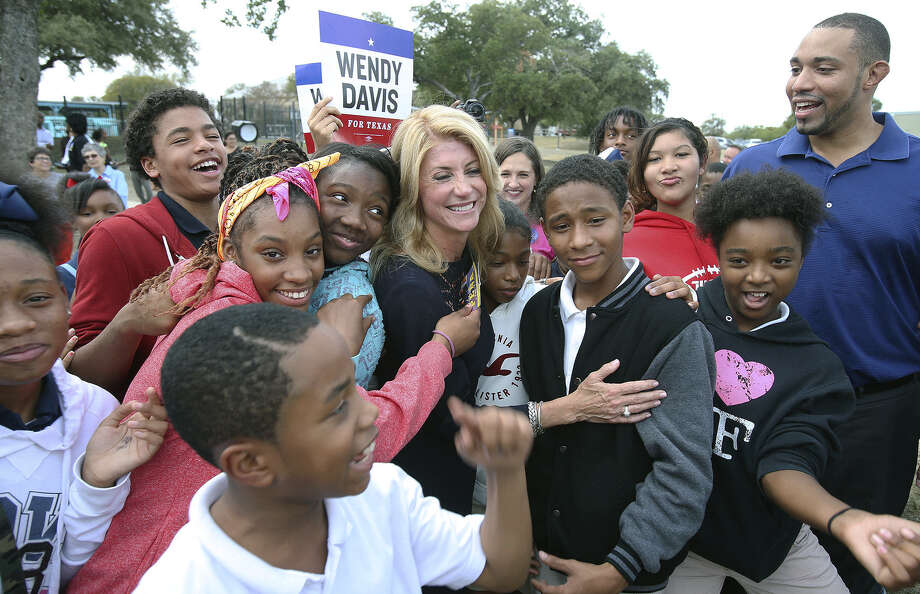 Children crowd around Democratic gubernatorial candidate Sen. Wendy Davis during her campaign stop with Tommy Calvert (right), who is running for Bexar County Commis- sioners Court, at the Claude Black Center on East Commerce Street. Photo: Tom Reel / San Antonio Express-News