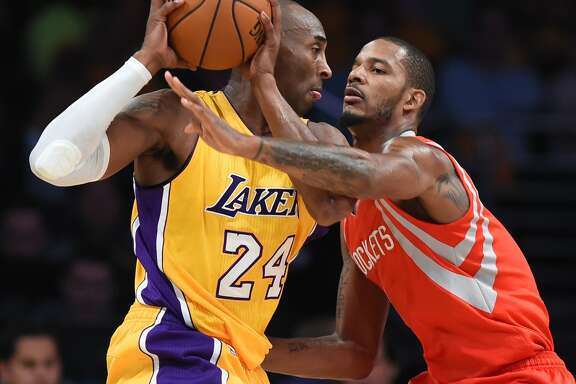 Kobe Bryant, left, goes against Rockets forward Trevor Ariza on Tuesday night in Bryant's first regular-season game since Dec. 17, 2013.