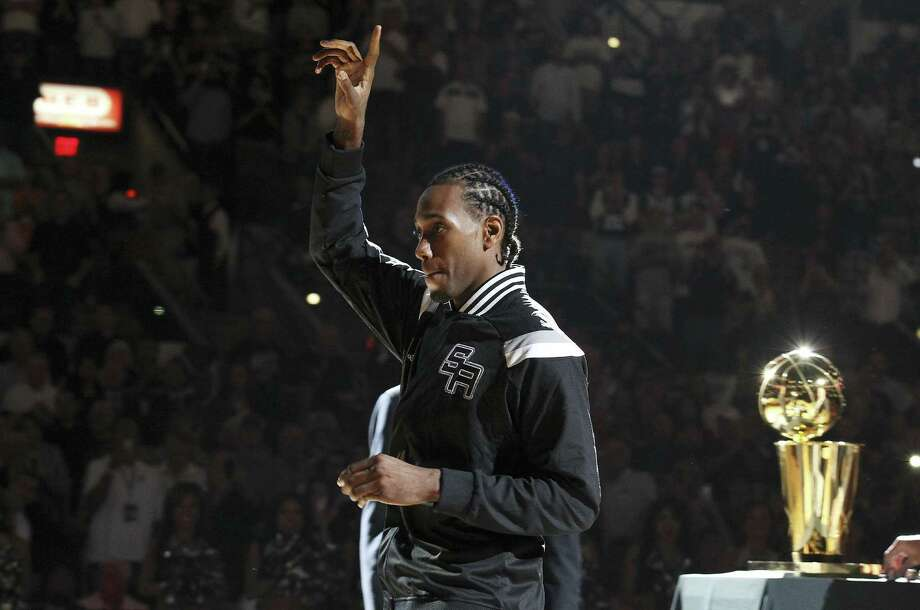 NBA Finals MVP Kawhi Leonard acknowledges the crowd after receiving his championship ring at the AT&T Center. He was cleared to play, but coach Gregg Popovich rested him. Photo: Kin Man Hui / San Antonio Express-News / ©2014 San Antonio Express-News