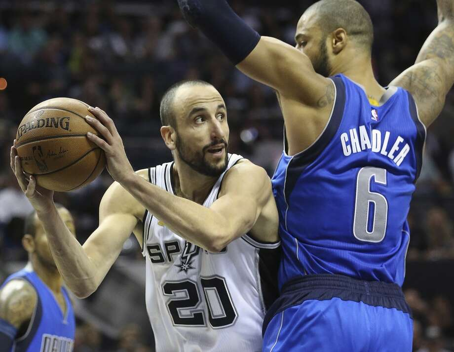 manu Ginobili looks to pass against Tyson Chandler as the Spurs open the season against the Dallas Mavericks at the AT&T Center  on October 28, 2014.