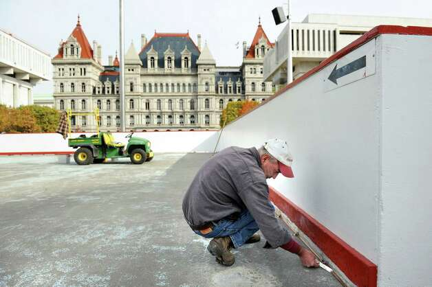 OGS worker Rob Fix tools off caulk at the base of the boards for the ice skating rink on Tuesday, Oct. 28, 2014, at the Empire State Plaza in Albany, N.Y. (Cindy Schultz / Times Union) Photo: Cindy Schultz