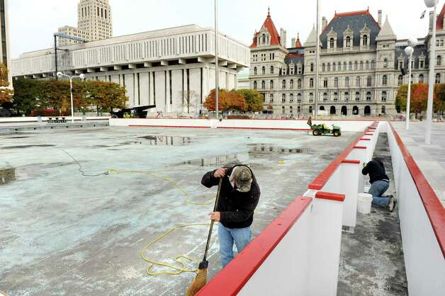 OGS worker Brian Dingman, left, sweeps debris as Joseph Johnson secures the boards for the ice skating rink on Tuesday, Oct. 28, 2014, at the Empire State Plaza in Albany, N.Y. (Cindy Schultz / Times Union) Photo: Cindy Schultz