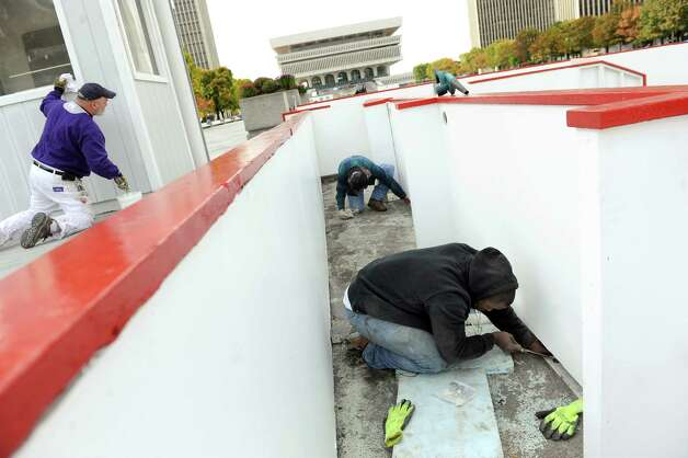 OGS worker Rick Cramer, left, paints a service building as Joseph Johnson, right, and Dave Cootware secure the boards for the ice skating rink on Tuesday, Oct. 28, 2014, at the Empire State Plaza in Albany, N.Y. (Cindy Schultz / Times Union) Photo: Cindy Schultz