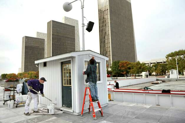 OGS workers Rick Cramer, left, and Pete Wowk, center, paint a small service building for the ice skating rink on Tuesday, Oct. 28, 2014, at the Empire State Plaza in Albany, N.Y. (Cindy Schultz / Times Union) Photo: Cindy Schultz