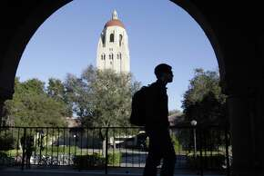 A Stanford University student walks in front of Hoover Tower on the Stanford University campus in Palo Alto, California. Financial habits students learn as a freshman can make a huge difference down the line about budgeting, the risks of using credit cards and other money issues, financial advisers say.