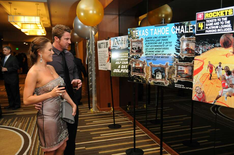 Melanie Mabry, left, of Spring, and Lee Loyd, of Houston, check out the live auction items at the Legacies of Spring Branch Gala. Photo: Jerry Baker, For The Chronicle