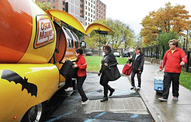 Delivering lunches, from left, Oscar Mayer Hotdogger Alexandra Longo, Colita Willis, and Laurie Bills of the Meals on Wheels program of Senior Services of Albany, and Hotdogger Matt Heng load coolers into the Wienermobile Wednesday Oct. 29, 2014, in Albany, NY..  (John Carl D'Annibale / Times Union) Photo: John Carl D'Annibale / 00029254A