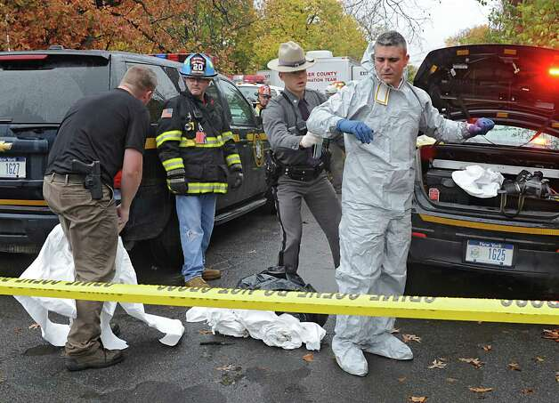 A state trooper sprays down a couple of other state troopers with bug spray after they leaving a cat hoarder's house on Wednesday, Oct. 29, 2014 in Schaghticoke, N.Y.  The police were removing the last of about 150 cats from the deplorable home. (Lori Van Buren / Times Union) Photo: Lori Van Buren / 00029244A