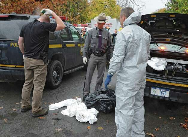 State troopers spray themselves with bug spray after they left a cat hoarder's house on Wednesday, Oct. 29, 2014 in Schaghticoke, N.Y. The police were removing the last of about 150 cats from the deplorable home. After spraying themselves, the same trooper's got suited up in the hazmat suits with tape and gas masks and re-entered the house again.  (Lori Van Buren / Times Union) Photo: Lori Van Buren / 00029244A