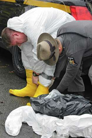 A state trooper helps another state trooper get re-suited to go back into a cat hoarder's house on Wednesday, Oct. 29, 2014 in Schaghticoke, N.Y.  The police were removing the last of about 150 cats from the deplorable home. (Lori Van Buren / Times Union) Photo: Lori Van Buren / 00029244A