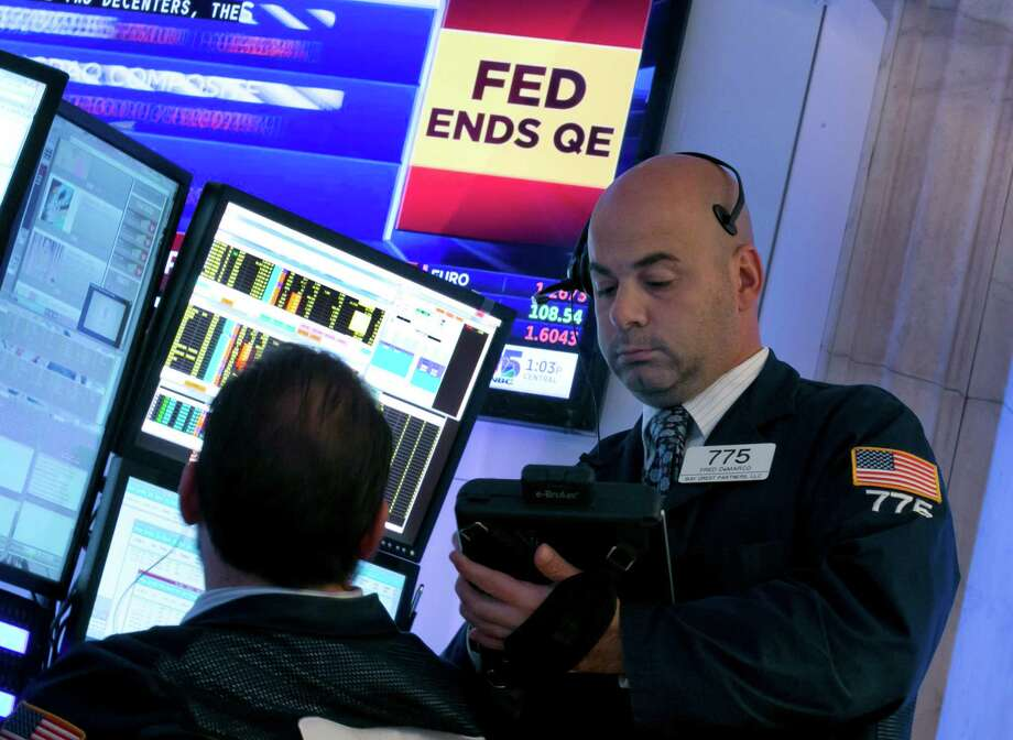 Trader Fred DeMarco, right, works on the floor of the New York Stock Exchange, as a television screen shows the decision of the Federal Reserve, Wednesday, Oct. 29, 2014.  The Fed plans to keep a key interest rate at a record low to support a U.S. job market that's improving but still isn't fully healthy and help lift inflation from unusually low levels. As expected, it's also ending a bond purchase program that was intended to keep long-term rates low. (AP Photo/Richard Drew) Photo: Richard Drew / Associated Press / AP