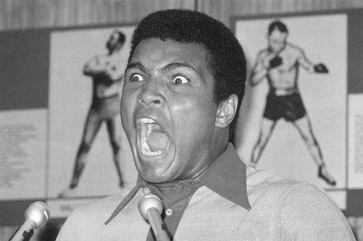 Aug. 29: Boxer Muhammad Ali displays an array of facial calisthenics during a press luncheon in New York to promote the sale of tickets to Madison Square Garden where the battle against George Foreman in Zaire was to be shown in October on closed circuit television.