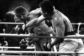 """FILE - In this Oct. 30, 1974, file photo, perspiration flies from the head of defending champion George Foreman as he takes a right from challenger Muhammad Ali in the seventh round in their world heavyweight championship bout dubbed """"Rumble in the Jungle"""" in Kinshasa, Zaire. Ali regained the world heavyweight crown by knocking out Foreman in the eighth round."""