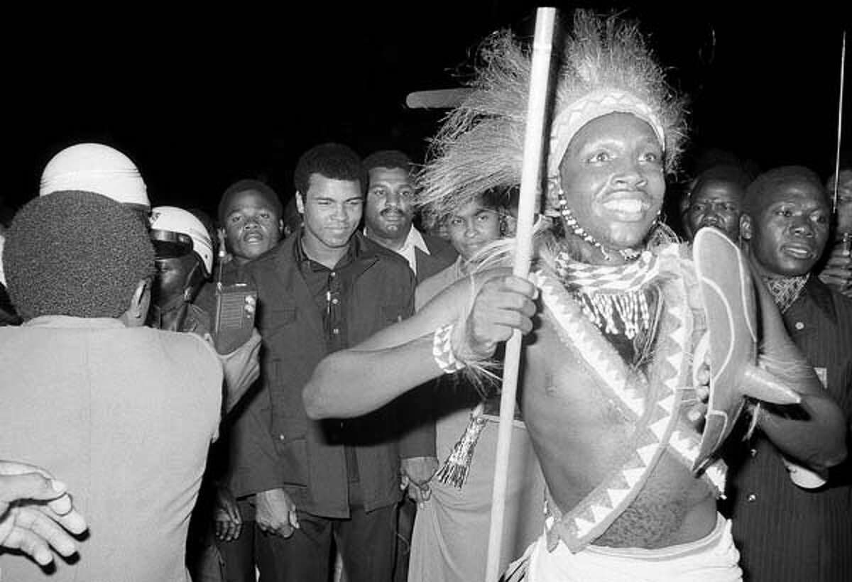 Sept. 10: Zaire dancer with spear moves ahead of Muhammad Ali through welcoming crowded at Kinshasa airport. Ali arrived in a chartered Air Zaire plane from Paris for the world championship fight with George Foreman.