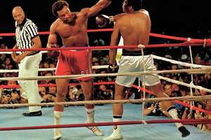 Muhammad Ali, right, deflects a punch by George Foreman, red shorts, in Kinshasa, Zaire, October 29, 1974.    Ali won the fight in Africa by a knock out in the 8th round.   Referee is Zack Clayton.