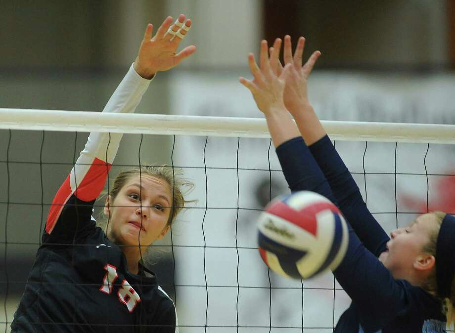 Churchill's Taylor Martinez (left) spikes the ball as Meghan Parker of Johnson defends during a high school volleyball match on Oct. 1. Photo: Billy Calzada / Billy Calzada / San Antonio Express-News / San Antonio Express-News
