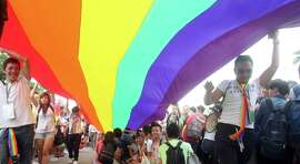 Participants revel through a street during a gay and lesbian parade in Taipei, Taiwan, Saturday. Thousands of gay and lesbian Taiwanese took to the streets showing Taiwan's acceptance of alternative lifestyles and activities from traditional ways of Chinese life.